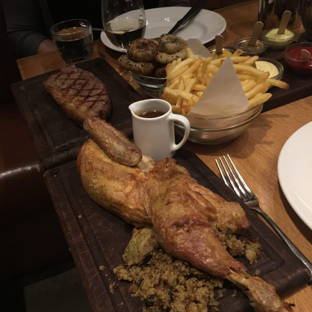 Tramshed: Chicken, steak on a table with some sides.